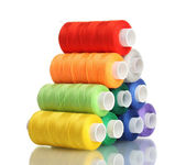 Pyramid of many-coloured bobbins of thread isolated on white — Stock Photo