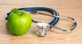 Estetoscopio médico y manzana verde sobre fondo de madera — Foto de Stock