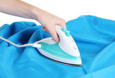 Electric iron on blue cloth isolated on white — Stock Photo