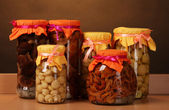 Delicious marinated mushrooms in the glass jars on wooden shelf — Stock Photo