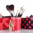 Red glass with brushes and makeup bag with cosmetics isolated on white — Stock Photo #8221963