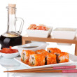 Delicious sushi on plate, chopsticks, soy sauce, fish and shrimps isolated — Stock Photo #8227013