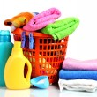 Clothes with detergent and washing powder in orange plastic basket isolated — Stock Photo #8227029