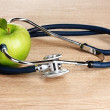 Medical stethoscope and green apple on wooden background — Stock Photo