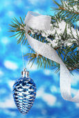 Christmas cone on the tree on blue — Stock Photo
