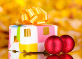 Christmas balls and gift on yellow background — Stok fotoğraf