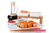 Delicious sushi on plate, chopsticks, soy sauce, fish and shrimps isolated — Stock Photo