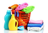Clothes with detergent and washing powder in orange plastic basket isolated — Stock Photo