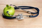 Estetoscópio médico e maçã verde sobre fundo de madeira — Foto Stock