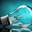 Light bulb on blue background — Stock Photo