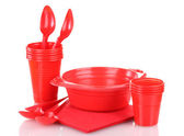 Bright red plastic tableware and napkins isolated on white — Stock Photo