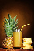 Рineapple juice and pineapple on brown — Stock Photo