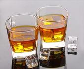 Два бокала шотландский виски и льда на серый стол — Стоковое фото