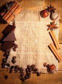 Coffee beans, cinnamon sticks, nuts and chocolate on sacking on wooden tabl — Stock Photo