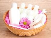Hotel amenities kit in basket on wooden background — Stock Photo