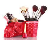 Vidro vermelho com pincéis e nécessaire com cosméticos isolado no branco — Fotografia Stock