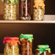 Delicious marinated mushrooms in the glass jars on wooden shelfs - Stock Photo