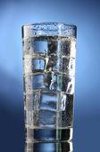 Vaso de agua con hielo sobre fondo azul — Foto de Stock