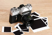 Old photo camera with photo papers on wooden background — Stock Photo