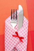 Fork and knife in a plaid cloth with a bow on a red tablecloth — Stock Photo