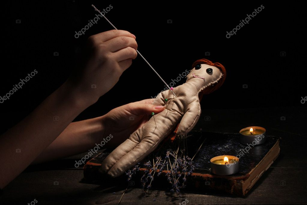 Voodoo doll girl pierced by a needle on a wooden table in the candlelight — Stock Photo #8271302