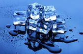 Melting ice cubes on blue background — Stock Photo