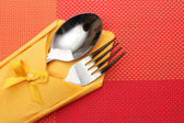 Fork and spoon in a yellow cloth with a bow on a red tablecloth — Stock Photo
