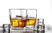 Iki bardak scotch viski ve buz üzerinde beyaz izole tablo — Stok fotoğraf