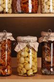 Délicieux champignons marinés dans les bocaux sur les étagères en bois — Photo