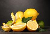 Olgun limon ve limes yapraklar gri arka plan üzerinde ahşap tablo — Stok fotoğraf