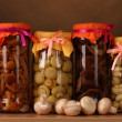 Delicious marinated mushrooms in the glass jars and raw champignons mushroo - Stock Photo