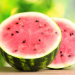Stock Photo: Ripe sweet watermelon on wooden table on green background
