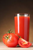 Tomato juice in glass and tomato on wooden table on brown backgr — Stock Photo