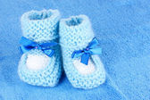 Blue baby booties on blue background — Stock Photo