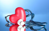 Estetoscópio médico e coração em fundo azul — Foto Stock