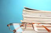 雑誌および青い背景上の眼鏡のスタック — ストック写真