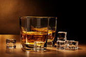 Two glasses of scotch whiskey and ice on wooden table on brown background — Stock Photo