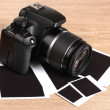 Digital photo camera with photo paper on wooden background - Stock Photo