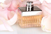 Perfume in a beautiful bottle and petals closeup — Stock Photo
