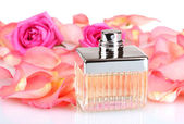 Perfume in a beautiful bottle, petals and pink roses isolated on white — Stock Photo