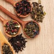 Different kinds of green and black dry tea in spoons on wooden table — Stock Photo