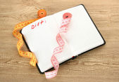 Planning of diet. Notebook and measuring tapes on wooden table — Stock Photo