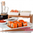 Delicious sushi on plate, chopsticks, soy sauce, fish and shrimps isolated - Stock Photo
