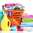 Clothes with detergent and washing powder in orange plastic basket isolated - Stock Photo