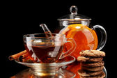 Glass teapot and cup with black fruit tea and cookies isolated on white — Stock Photo