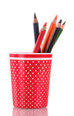 Red glass with colorful pencils isolated on white — Stock Photo