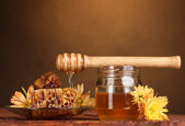 Jar of honey,honeycombs and wooden drizzler on table on yellow background — Stock Photo