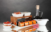 Delicious sushi on plate, chopsticks, soy sauce, fish and shrimps on gray b — Stock Photo