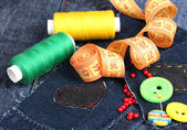 Heart-shaped patch on jeans with threads and buttons closeup — Stock Photo