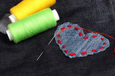 Heart-shaped patch on jeans with threads and needle closeup — Foto de Stock